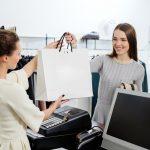 retail cashier giving a shopping bag to customer